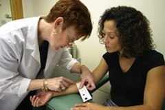A health care worker measures the size of the reaction to the tuberculin skin test © CDC