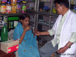 DOTS - A woman takes her TB drugs under supervision in a pharmacy