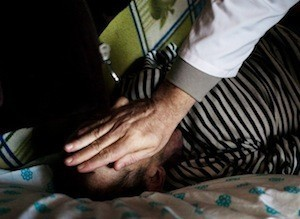 A doctor checks for signs of life and finds none, in a patient with drug resistant TB in the Ukraine © Misha Friedman/WHO